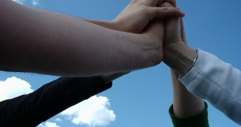 1280px-Team_touching_hands[1]
